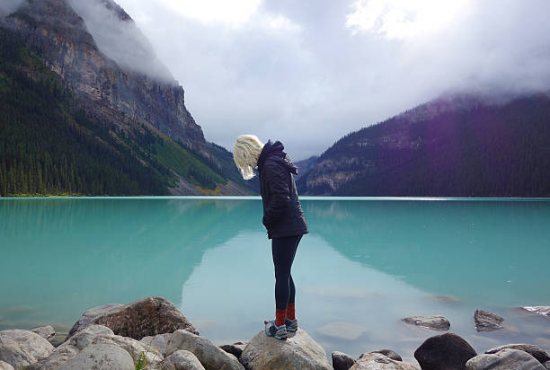young woman looking away from camera at turquoise lake lousie - lake louise stockfoto's en -beelden