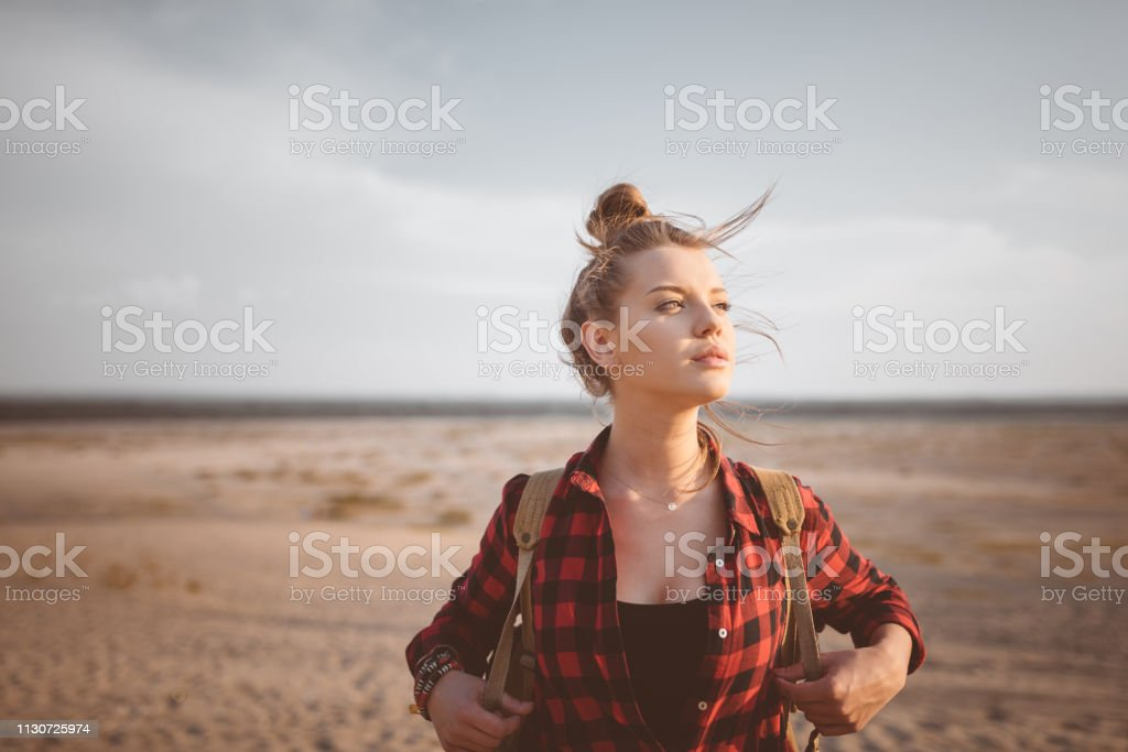 Young woman looking away in desert against sky Thoughtful blond young woman standing against sky. Beautiful hipster is hiking in desert. Female explorer is looking away. 20-24 Years Stock Photo