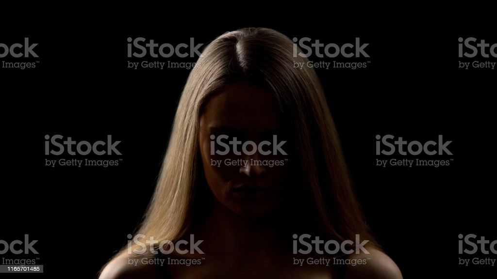 Young woman looking down, fighting with fears, lack of confidence,...