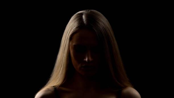 joven mirando hacia abajo, luchando con miedos, falta de confianza, complejos - human trafficking fotografías e imágenes de stock