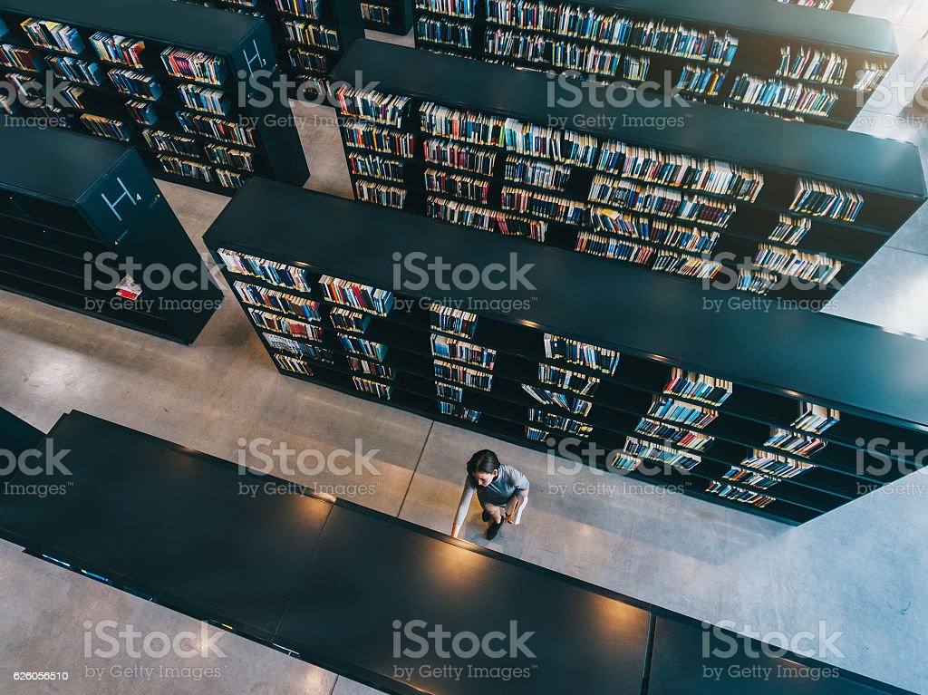 Young woman looking for a book in shelf stock photo