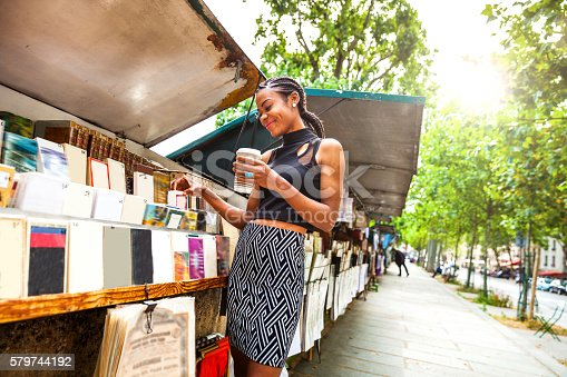 istock Young woman looking for books in a kiosk in Paris 579744192
