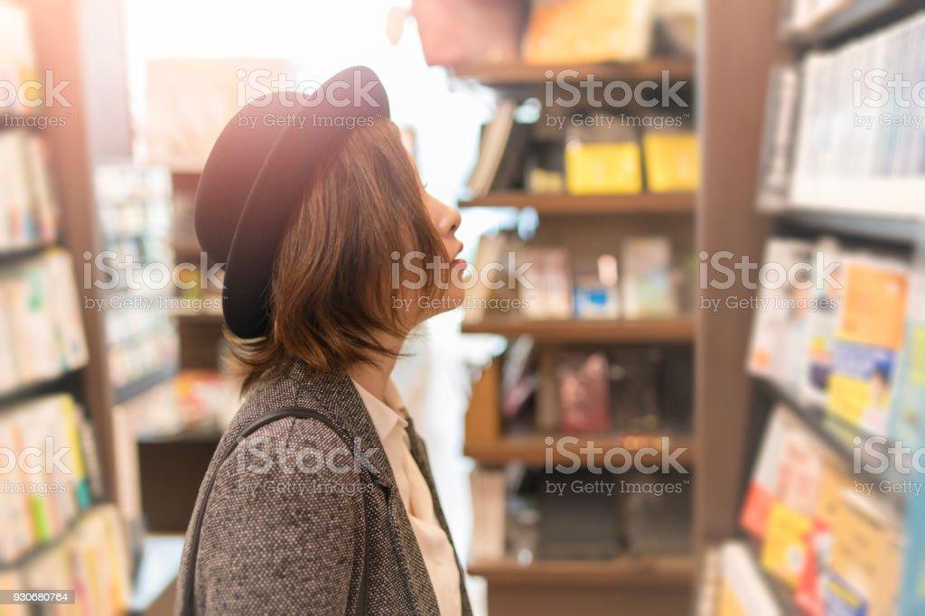 Junge Frau auf der Suche nach Bücher im store – Foto