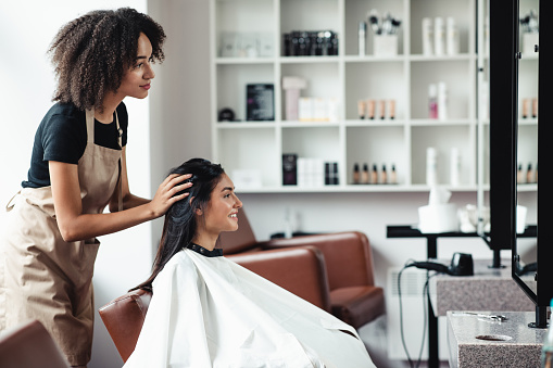 Young woman looking for changes, trying new hairstyle at beauty salon, empty space