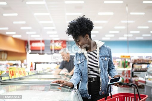 istock Young woman looking for products in the supermarket freezer 1183448347