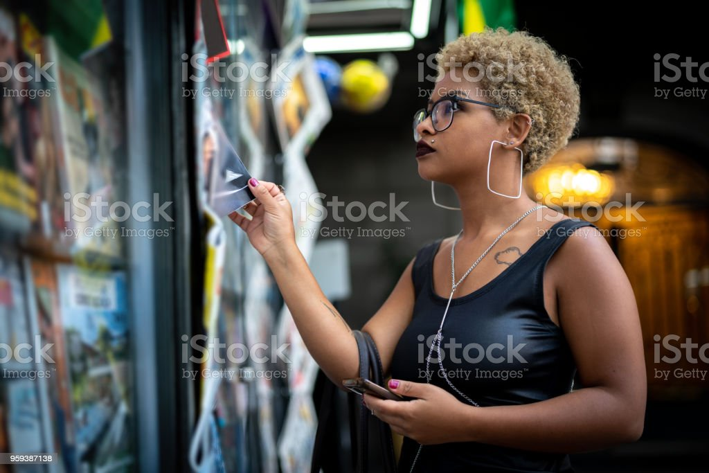 Young Woman looking for the news at newsstand stock photo