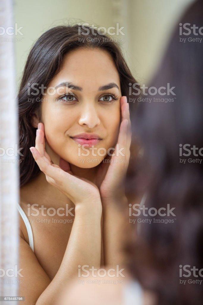 Genç kadın banyo aynaya bakıyorum royalty-free stock photo