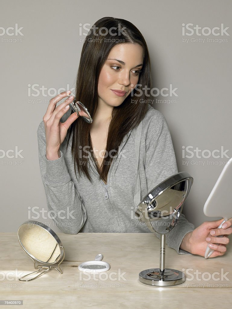 Young woman looking in mirror stock photo