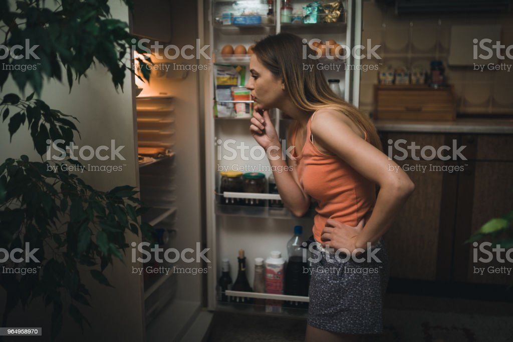 Young woman looking in the refrigerator late night stock photo