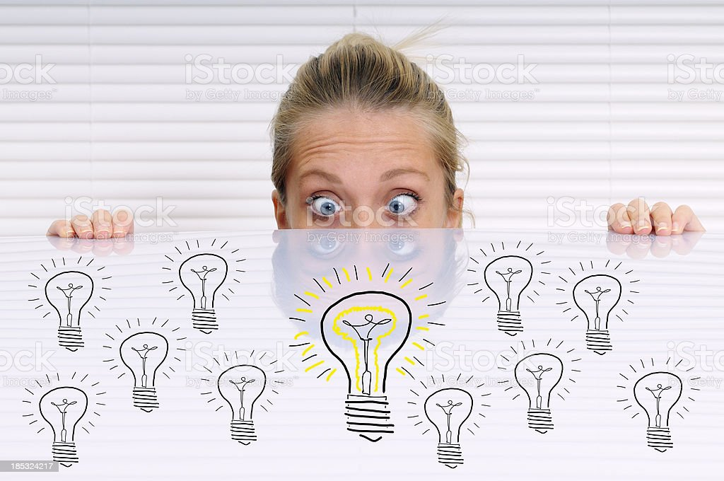 Young woman Looking Light Bulbs Sketched on Whiteboard royalty-free stock photo