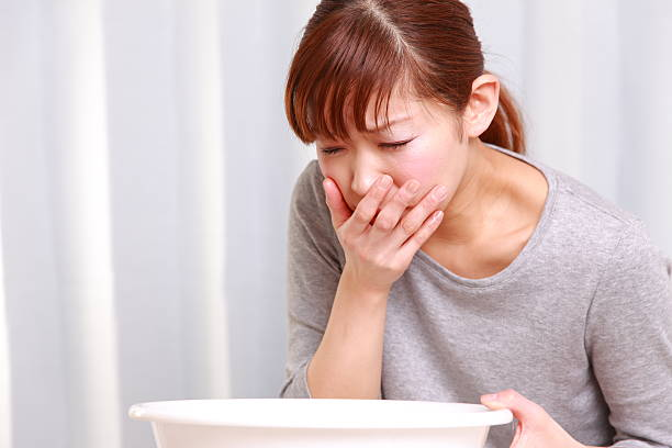 Young woman looking nauseous with hand over mouth stock photo