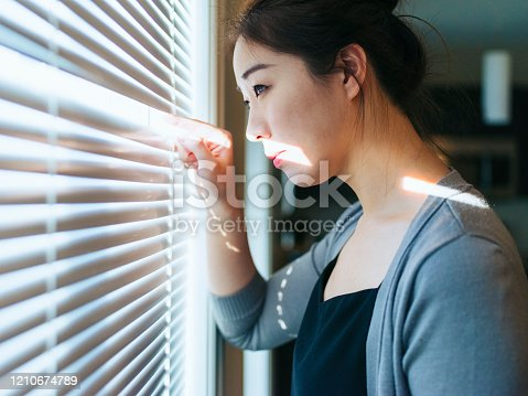 young woman looking out of blinds at home.
