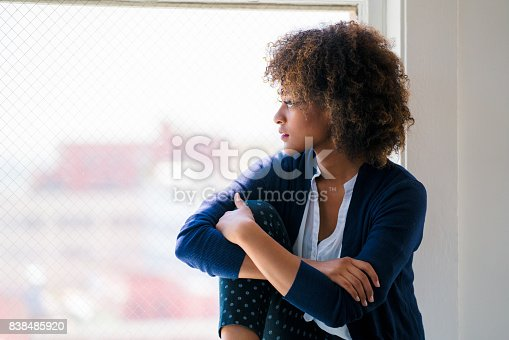 istock Young woman looking out of the window 838485920
