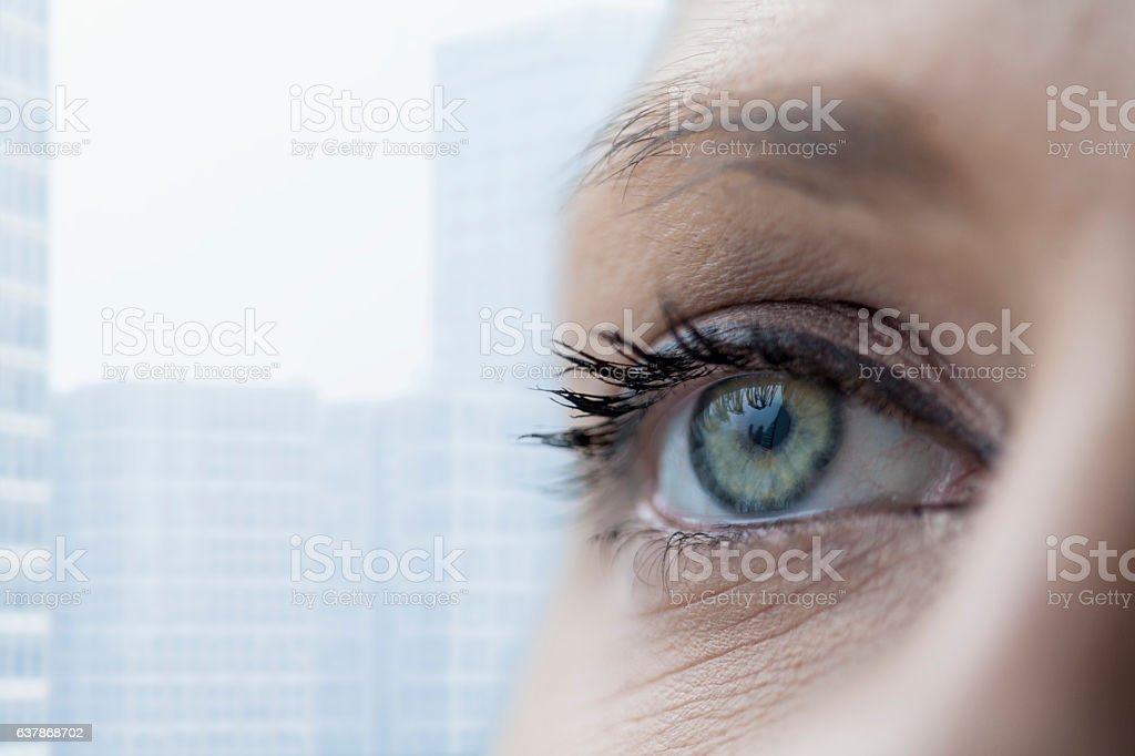 Young woman looking out of window at cityscape stock photo