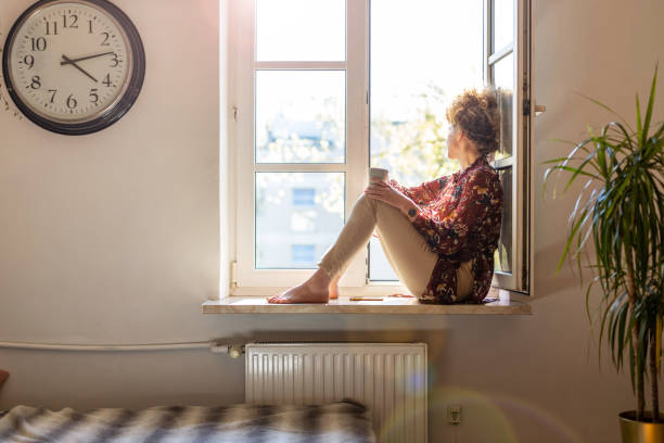 young woman looking out of window - trap house stock pictures, royalty-free photos & images