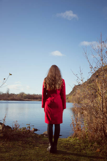 Young woman looking out over a lake stock photo