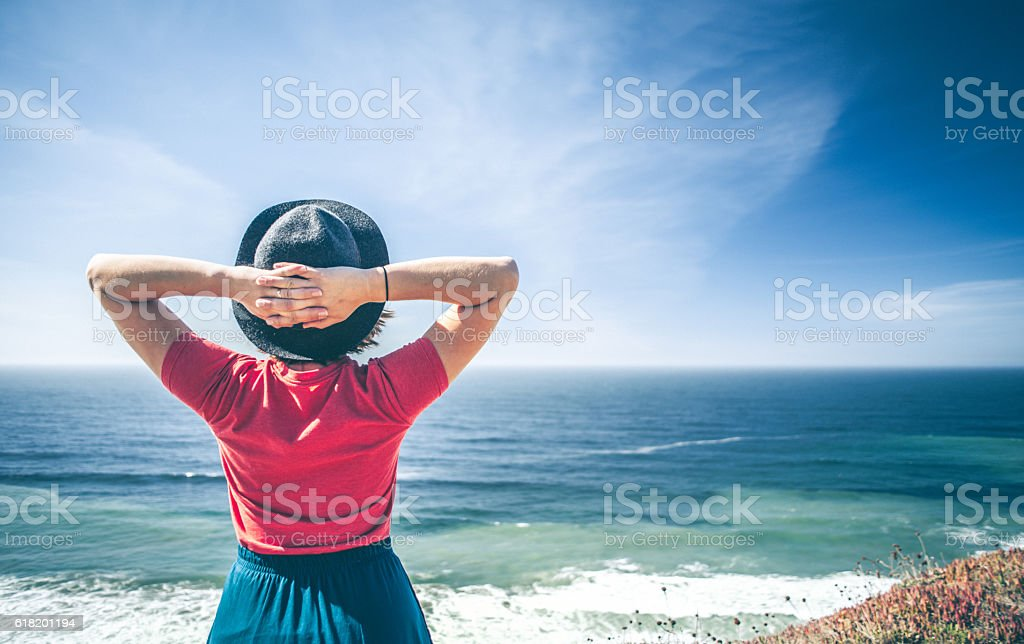 Young woman looking out over the ocean. stock photo