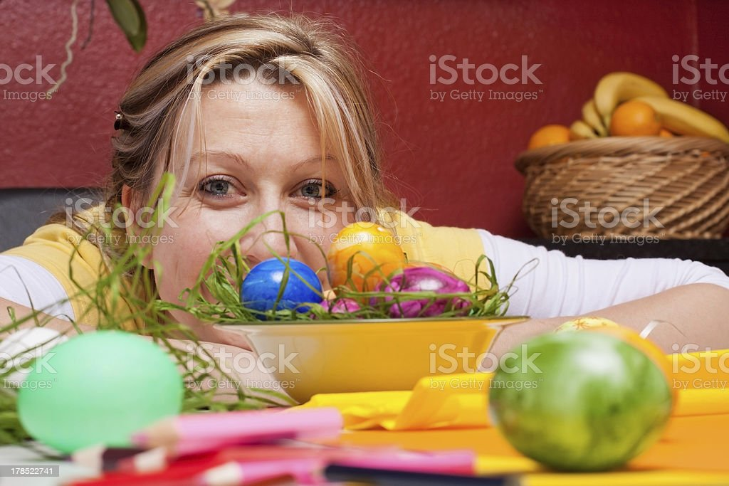 Young woman looking over colorful easter eggs royalty-free stock photo