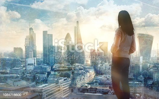 istock Young woman looking over the City of London at sun set. Future, new business opportunity and business success concept. 1054718600