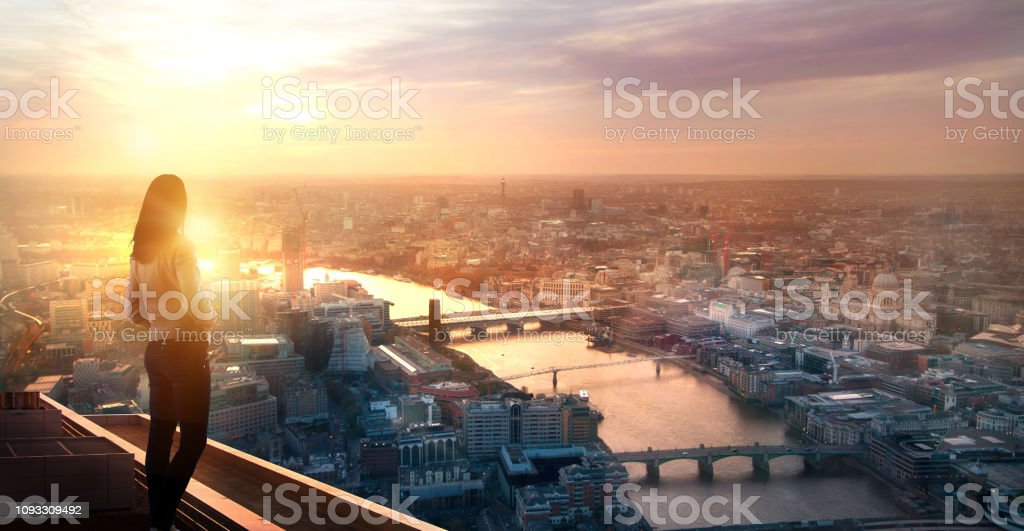 Young woman looking over the City of London at sunset. Future, new business opportunity and business success concept. stock photo