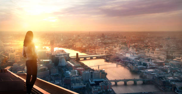 Young woman looking over the City of London at sunset. Future, new business opportunity and business success concept. Young woman looking over the City of London at sun set. Future, new business opportunity and business success concept. fresh start morning stock pictures, royalty-free photos & images