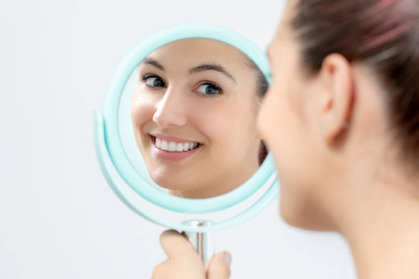 Young woman looking reviewing teeth whitening in mirror. stock photo