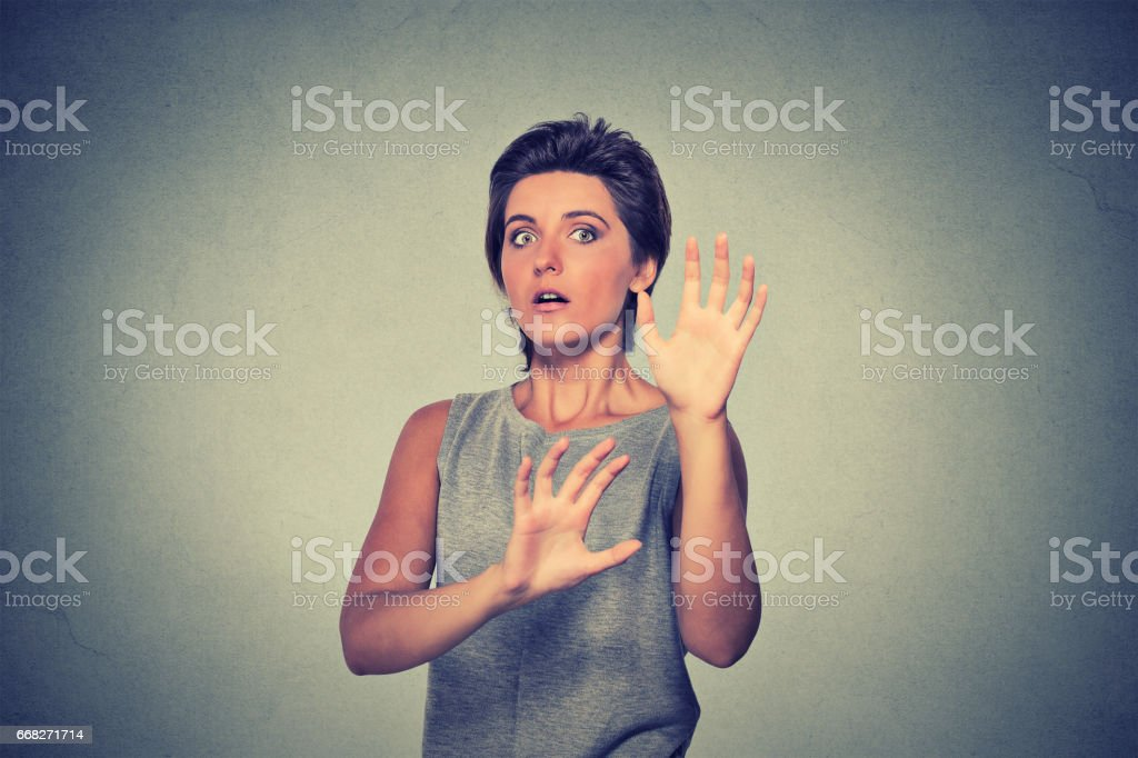 Young woman looking shocked scared trying to protect herself foto stock royalty-free