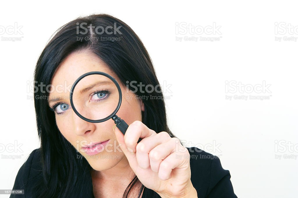 Young woman looking through a magnifying glass royalty-free stock photo