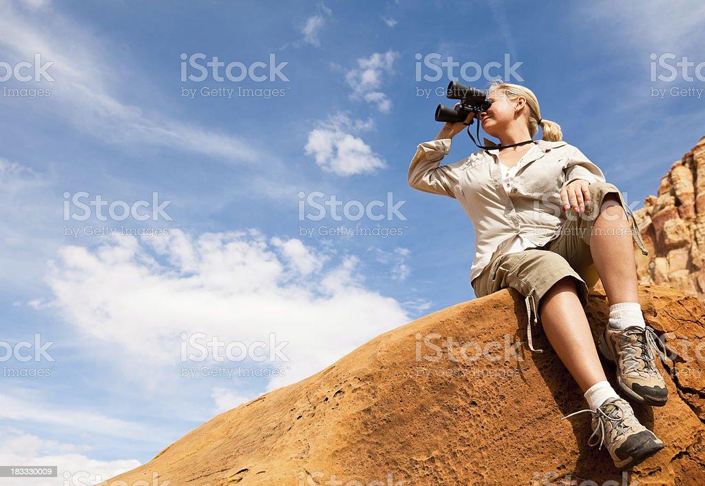 Young woman looking through binoculars royalty-free stock photo