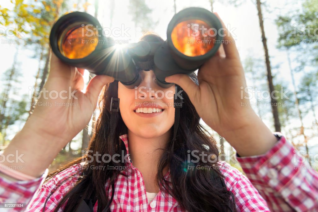 Young woman looking through binoculars stock photo