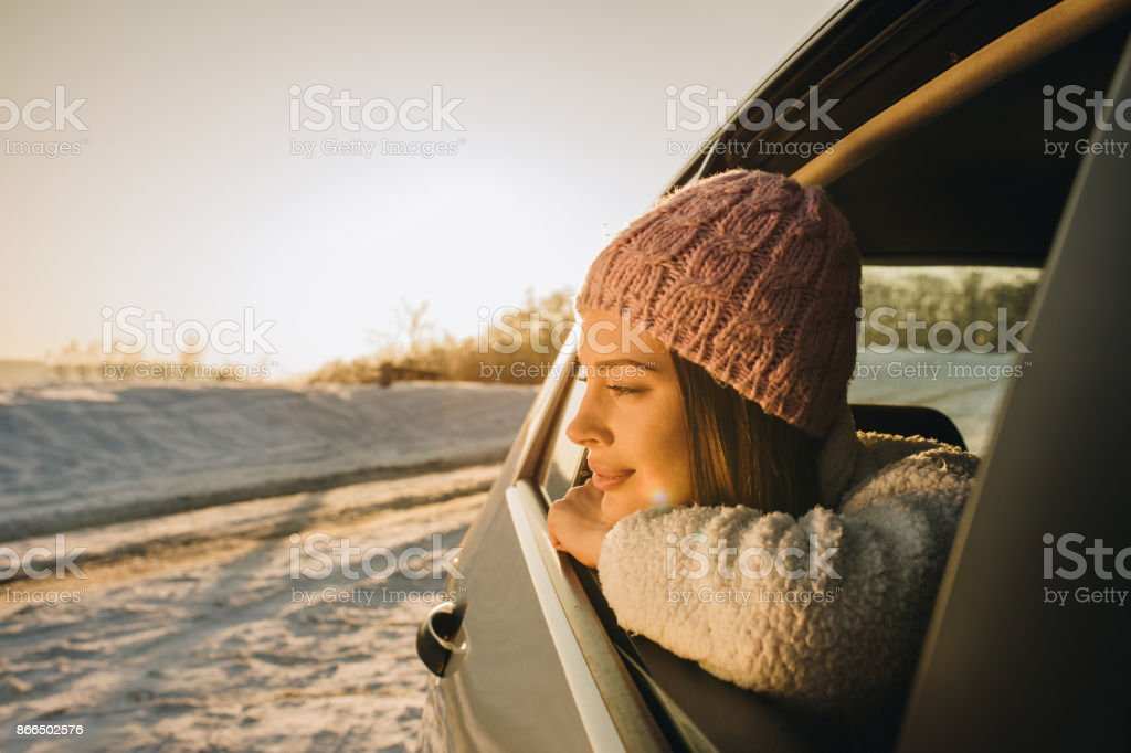 Smiling pensive woman enjoying in winter day at sunset while looking...