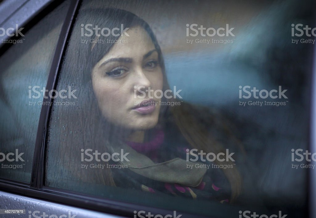 Young woman looking through car window stock photo