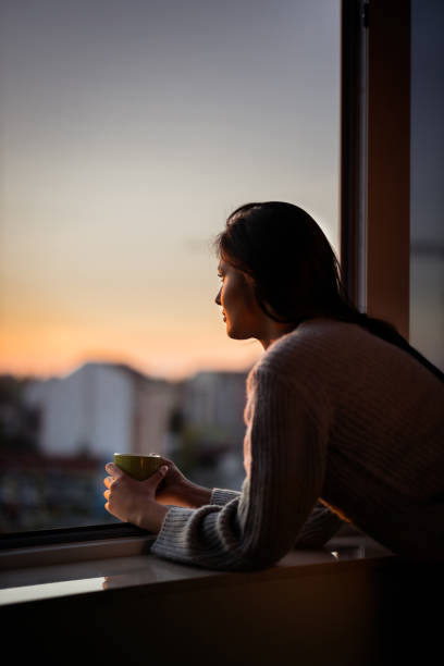 Young woman looking through window during coffee time. stock photo