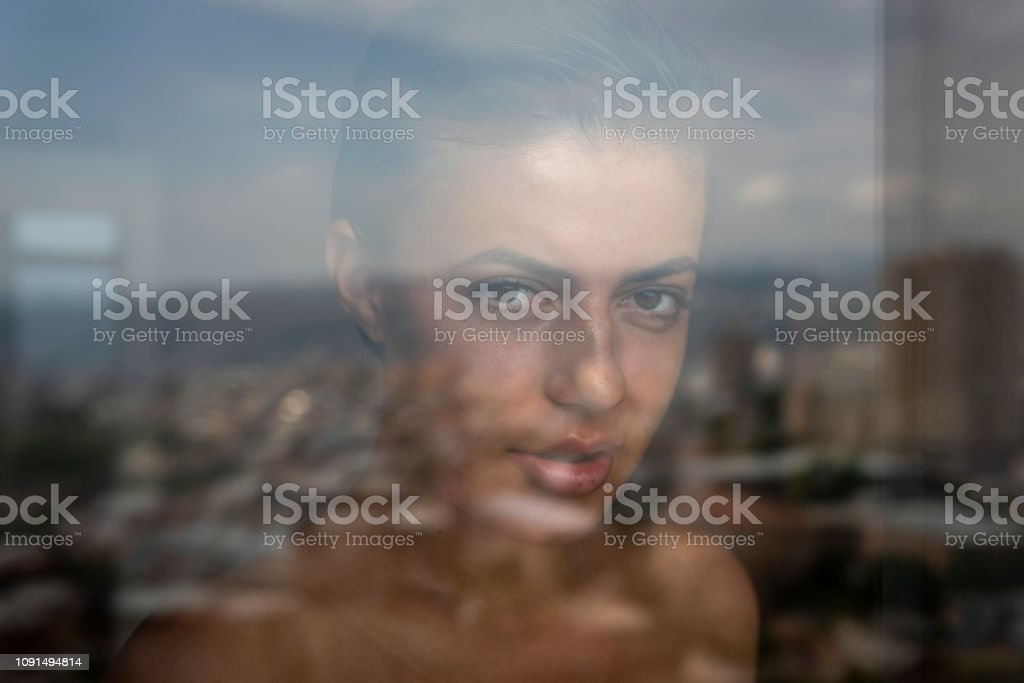 A young woman gazes through a glass window in an apartment in a city,...