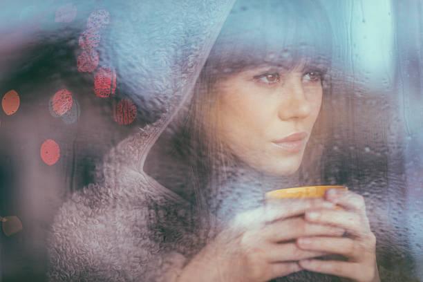 junge frau blick durchs fenster an regnerischen tag - gesichtertassen stock-fotos und bilder