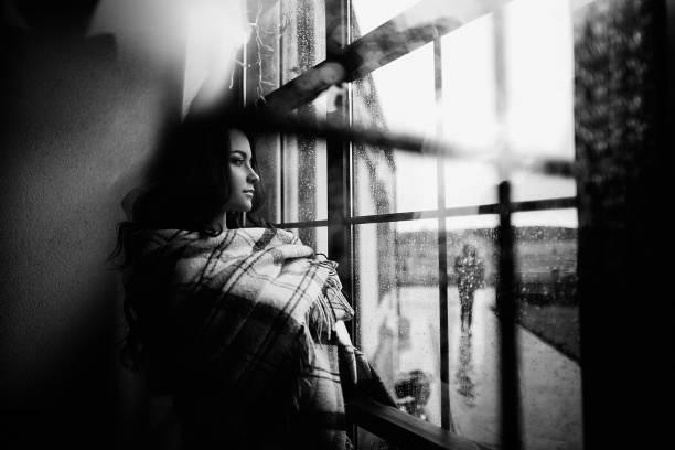 Jeune femme regardant à travers une fenêtre - Photo