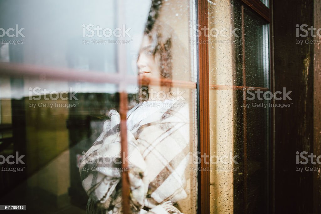 Portrait of young caucasian woman looking through window.