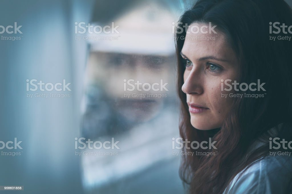 Young woman looking through window with reflection stock photo