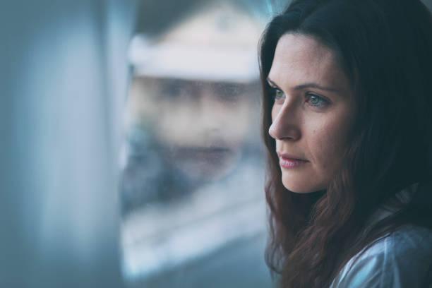 Junge Frau, die durch Fenster mit Reflexion – Foto
