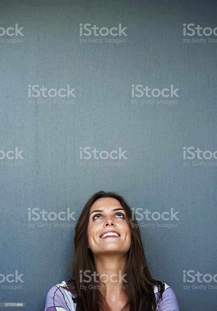 Young woman looking up at copyspace against grey background stock photo