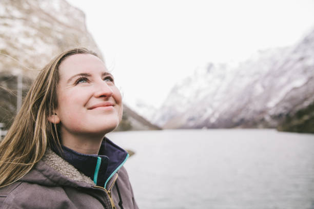 Young Woman Looking Up at Fjords stock photo