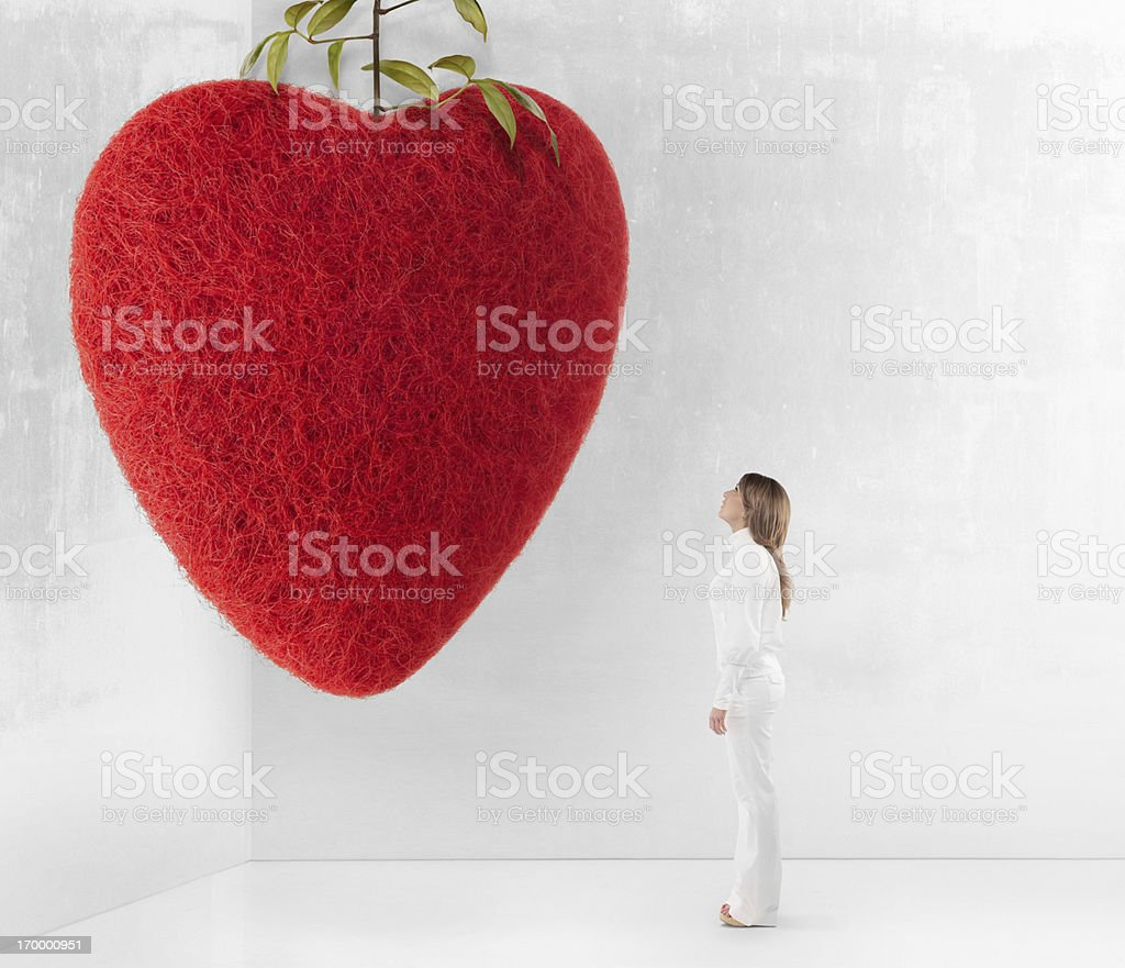 Young woman looking up at giant red felt heart royalty-free stock photo
