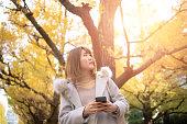 秋の銀杏の木を見上げて若い女性
