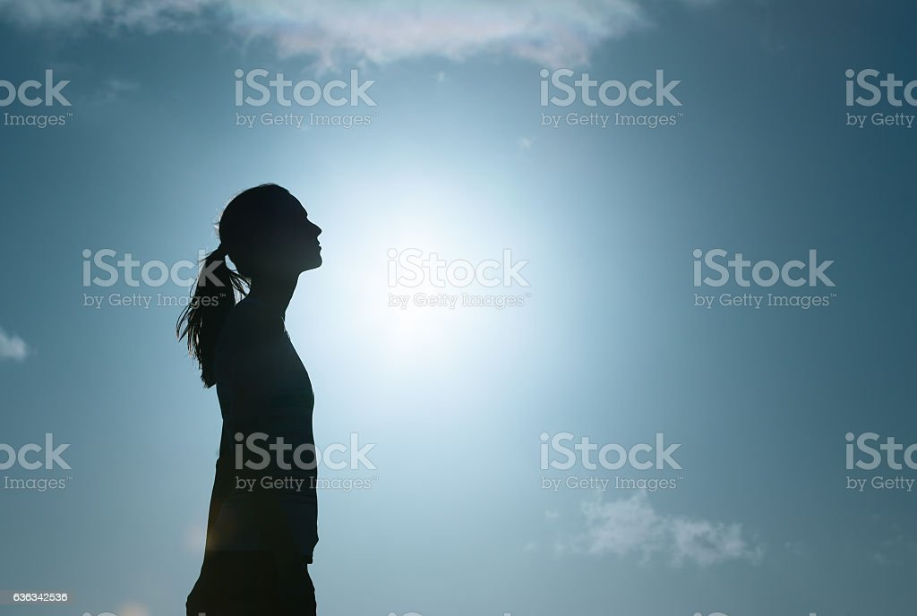 Young woman looking up into the sky stock photo