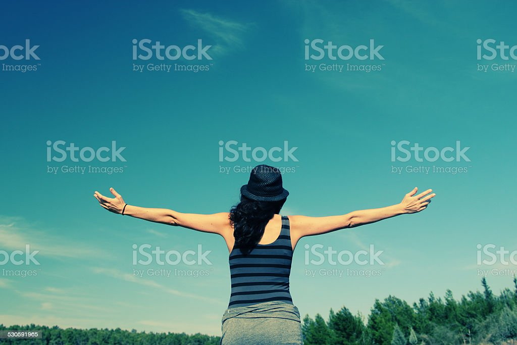 young woman looking up with open arms stock photo