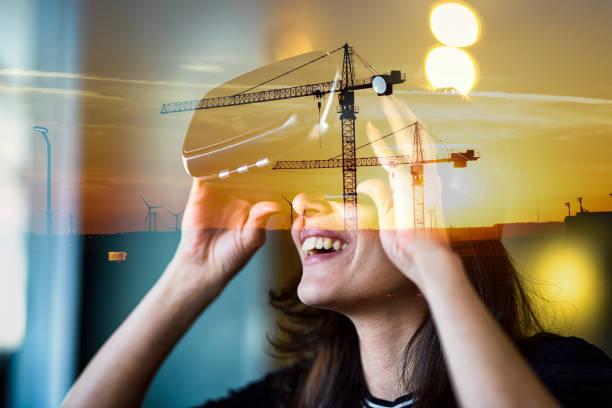 Junge Frau mit VR hinter der gläsernen Reflexion von Stadtansicht und Baustelle auf Fenster, doppelte Exposition – Foto