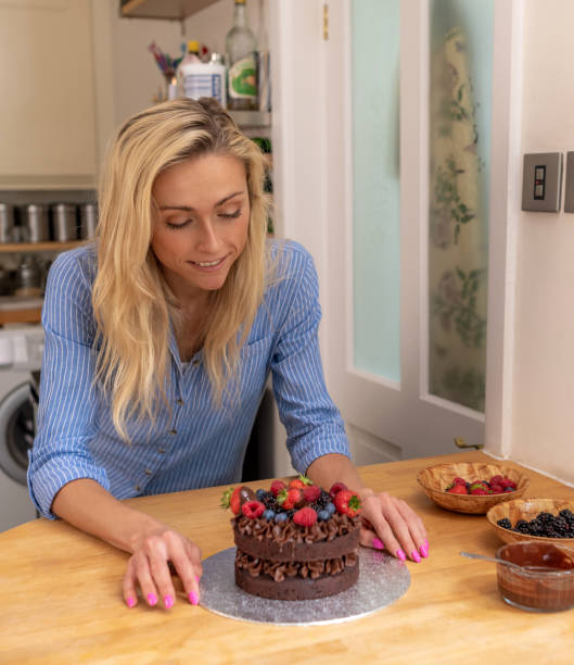 Young woman looks at a home-made chocolate cake stock photo