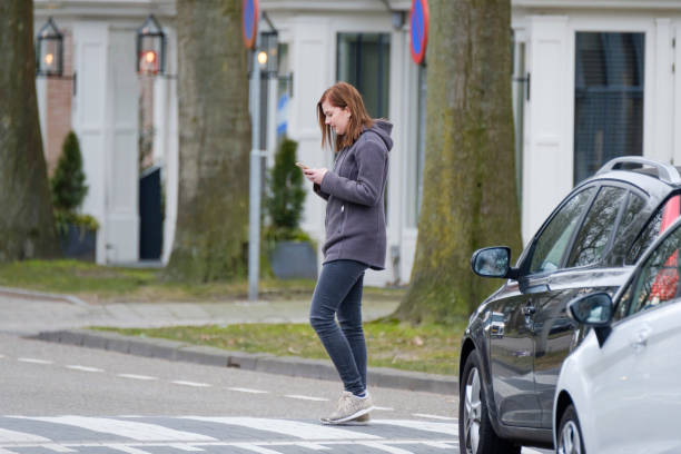 jonge vrouw kijkt op haar mobiel en betaalt geen aandacht voor verkeer - voetganger stockfoto's en -beelden