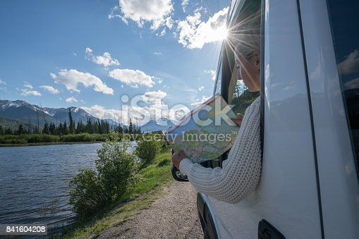 841604240 istock photo Young woman looks at road map near mountain lake 841604208