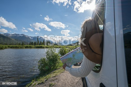 841604240 istock photo Young woman looks at road map near mountain lake 841604238